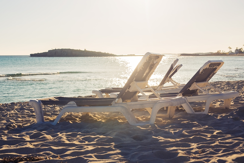 Sunbeds on the sea beach during sunset.